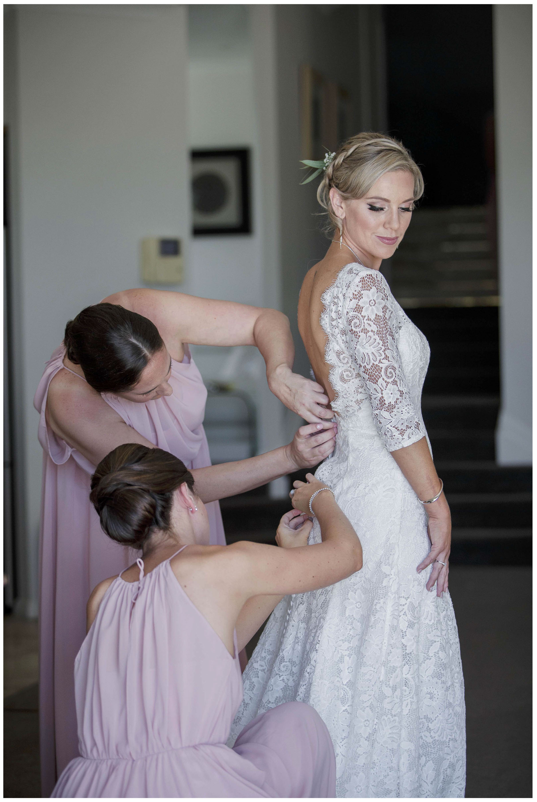 Bridesmaids in lilac dresses botton the bride's white lace wedding dresss
