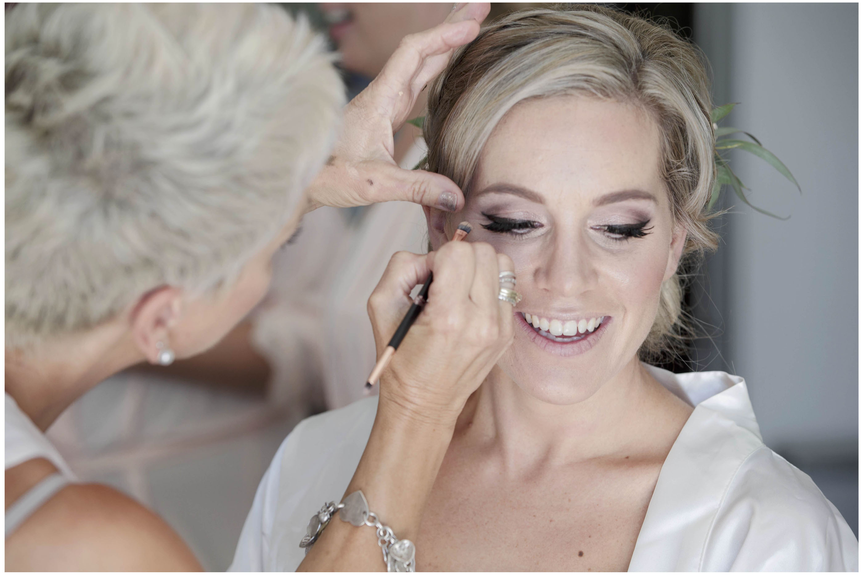 Bride has her wedding makeup and haair styled, Flowers in brides hair, Auckland Wedding Photographers, Bridesmaids laugh as they look on, Five Knotts Wedding Venue