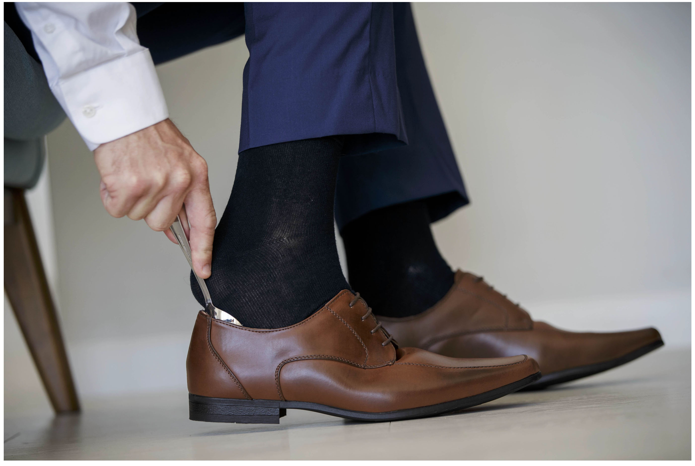 Groom used a spoonn to help on wedding shoes, Auckland Wedding Photographers, Five Knotts Wedding venue,