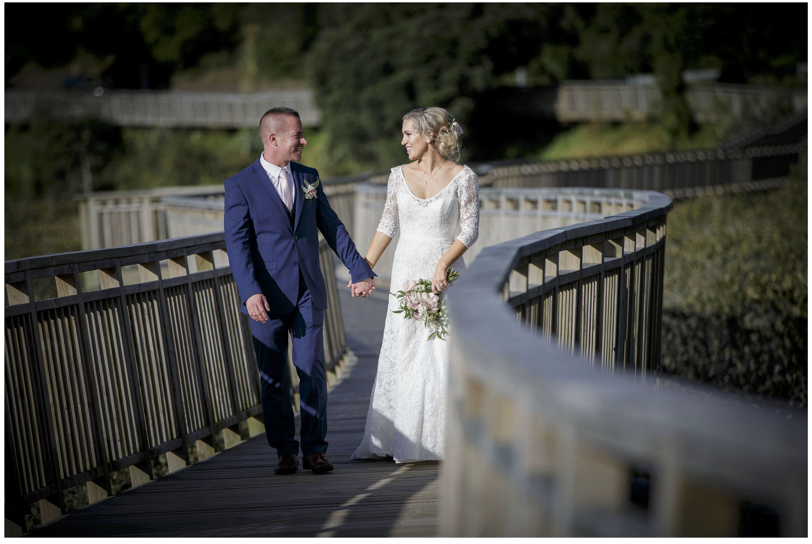 Bride in White Lacetop Dress with groom on bordwalk Remuers Auckland, Auckland Wedding Photographers