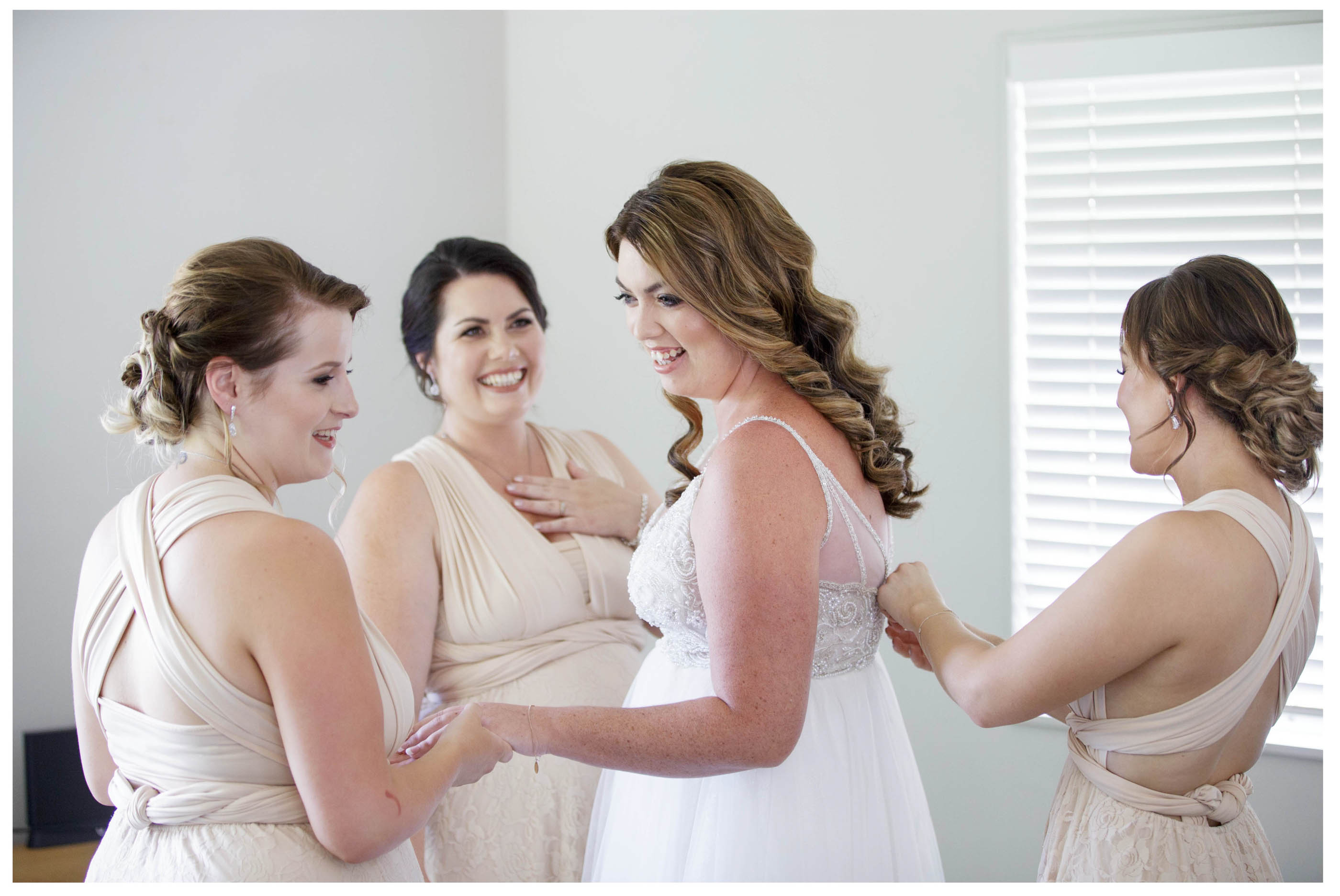 Bride in her wedding dress with bridesmaids