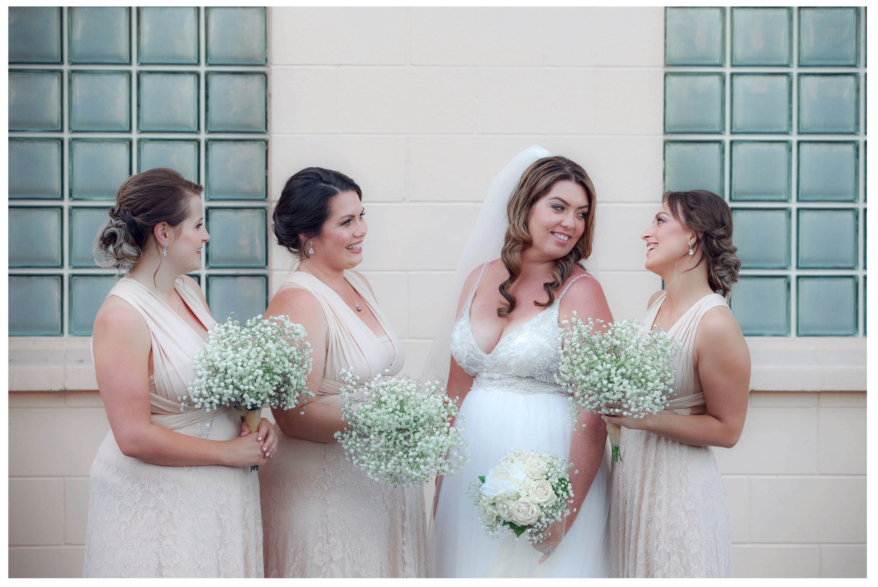 Bride and bridesmaids pose infromt of wall with glass block windows